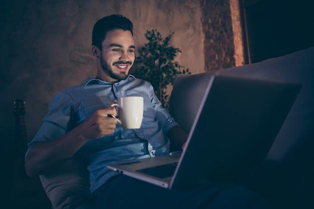 Uomo seduto sul divano e lavora al computer portatile