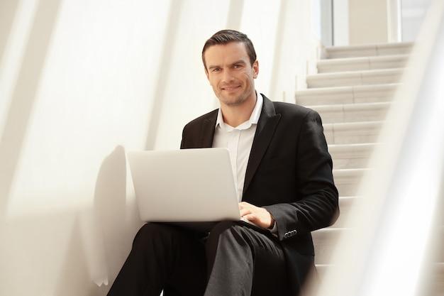Uomo seduto sulle scale e che usa il laptop