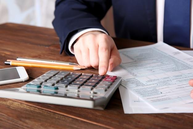 Uomo seduto a tavola con calcolatrice e documento