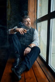 Uomo seduto sul davanzale della finestra e fuma un sigaro, interni ufficio vintage. cultura del fumo di tabacco, sapore specifico. il fumatore maschio guarda la finestra