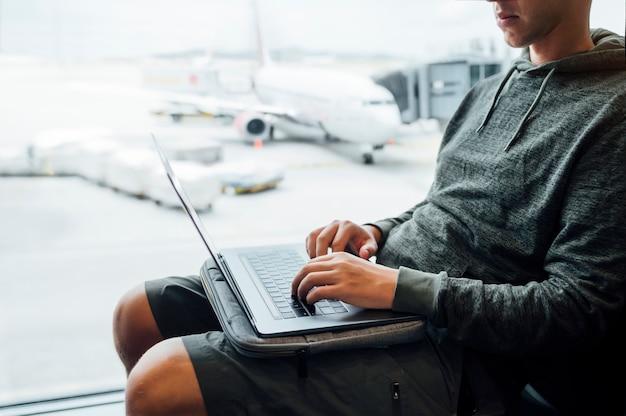 Uomo che si siede con il computer portatile all'aeroporto