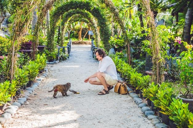 Uomo seduto con una scimmia in un giardino