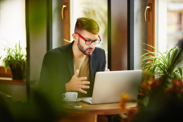 Uomo che si siede e lavora al computer portatile
