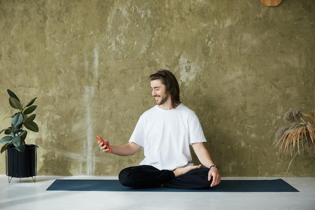 Uomo seduto in posa yoga sul tappetino utilizzando smartphone, bel maschio sorridente e tenendo il telefono mentre si fa yoga e meditazione