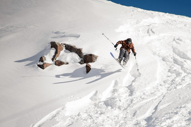 L'uomo sciare giù per la collina vicino alla roccia nella neve nella famosa località turistica di gudauri in georgia