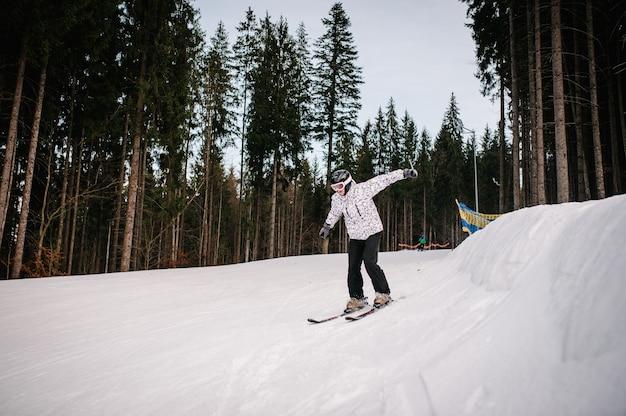 L'uomo sugli sci salta da una collina da un trampolino di lancio sulla neve in montagna
