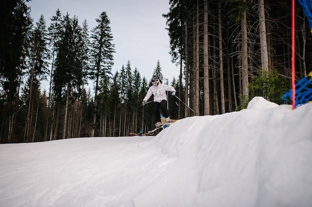 L'uomo sugli sci salta da una collina da un trampolino di lancio