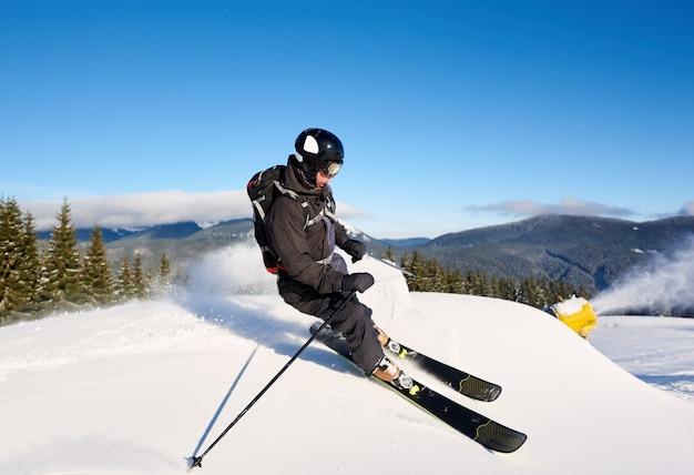 Sci uomo su pista preparata con neve fresca. macchina sparaneve che fa nevicate artificiali. natura magica sullo sfondo.