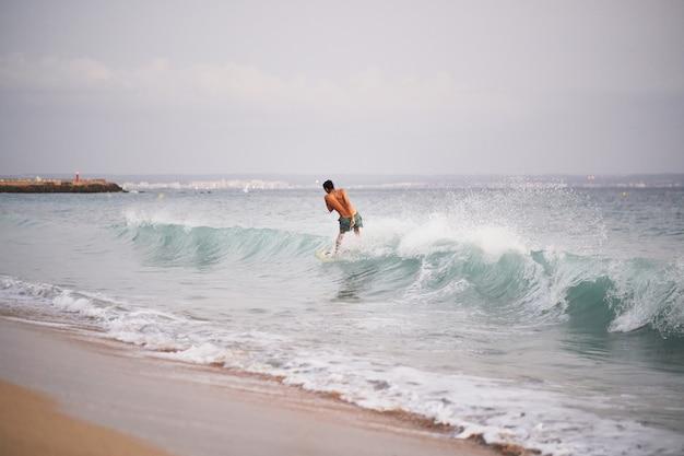 Uomo su uno skimboard che cattura un'onda in una spiaggia di palma de mallorca, spain