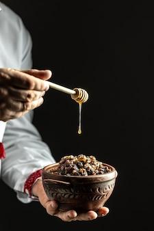Uomo in camicia slava che tiene ciotola con kutia tradizionale e versando miele