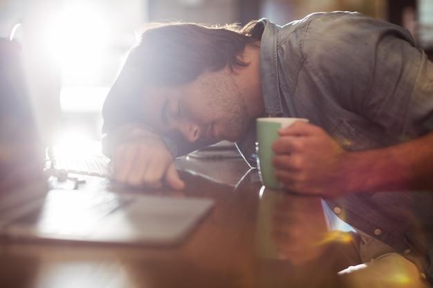 Uomo che dorme sul tavolo in ufficio