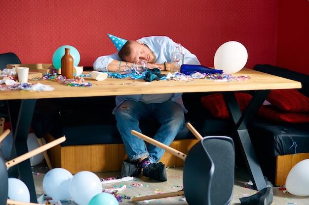 Uomo che dorme al tavolo con tappo blu nella stanza disordinata dopo la festa di compleanno, uomo stanco dopo la festa a casa