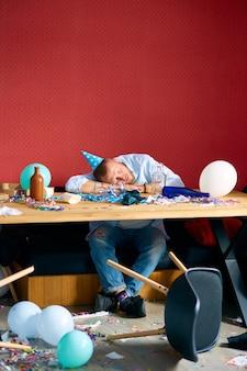 Uomo che dorme a tavola con un berretto blu in una stanza disordinata dopo la festa di compleanno