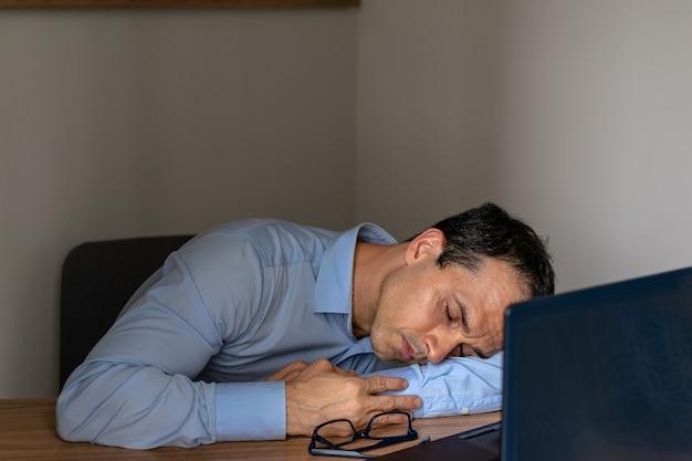 Uomo che dorme al lavoro con il suo laptop