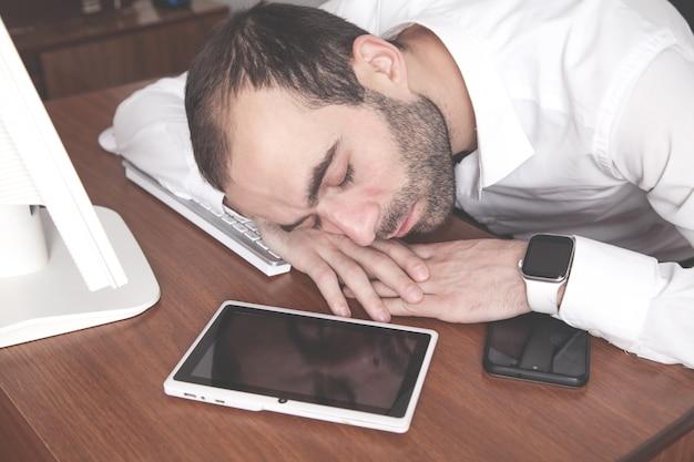 Uomo che dorme sul posto di lavoro in ufficio.