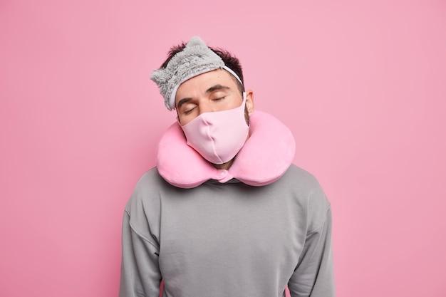 L'uomo dorme durante il viaggio durante il trasporto durante l'epidemia di coronavirus indossa una maschera protettiva per il sonno e il cuscino per dormire ha un pisolino vestito con un maglione casual