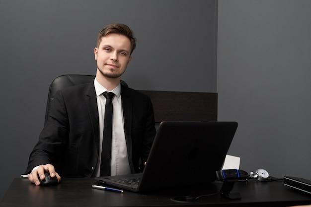 Uomo in vestito astuto che posa mentre lavorando con il rivelatore di bugia