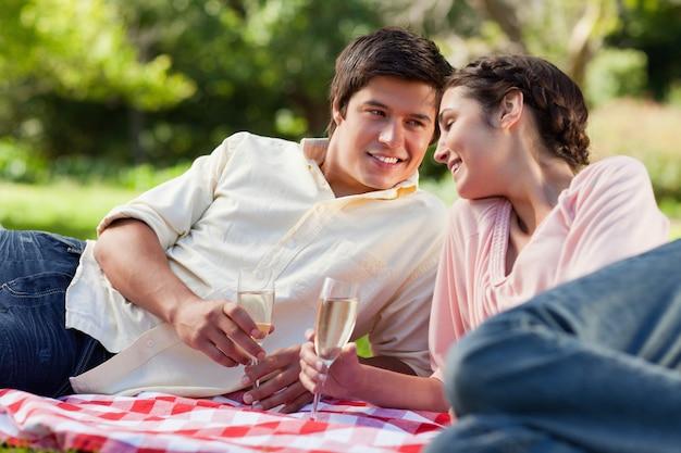 L'uomo sorride mentre guarda il suo amico durante un picnic