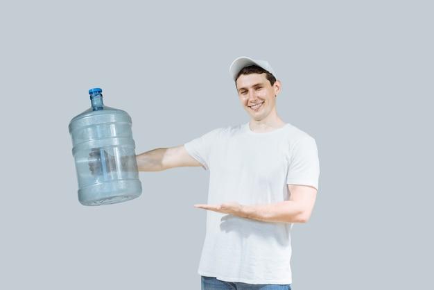Un uomo sorridente corriere erogando acqua in bottiglia a una maglietta bianca e cappuccio che trasporta un serbatoio di bevanda fresca e mostra la mano sull'acqua