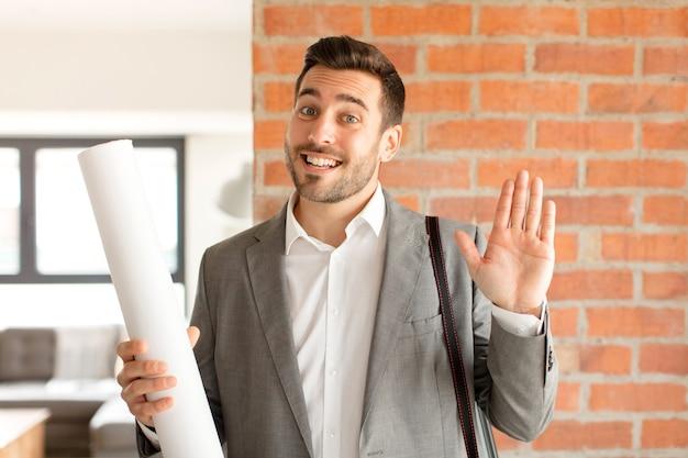 Uomo che sorride allegramente e allegramente, agitando la mano e salutandoti o salutandoti