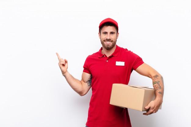 Uomo che sorride felicemente e che punta verso il lato e verso l'alto con entrambe le mani che mostrano l'oggetto nello spazio della copia Foto Premium