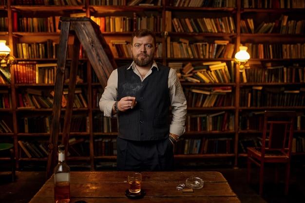 L'uomo fuma un sigaro, una bevanda alcolica in bottiglia sul tavolo, uno scaffale per libri e l'interno di un ufficio vintage sullo sfondo