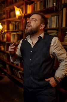 L'uomo fuma un sigaro e beve bevande alcoliche, scaffale per libri e interni ricchi di uffici sullo sfondo