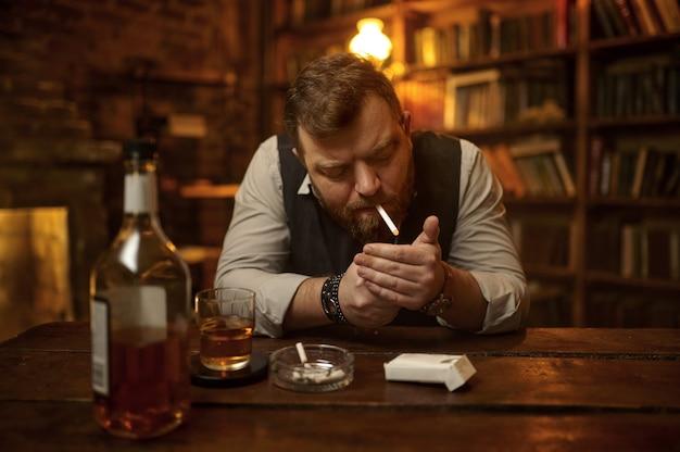 L'uomo fuma la sigaretta e beve la bevanda dell'alcool, la libreria e l'interno ricco dell'ufficio su priorità bassa. cultura del fumo di tabacco