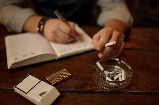 L'uomo fuma sigarette e scrive in taccuino, tabler in legno. cultura del fumo di tabacco, sapore specifico. fumatore maschio