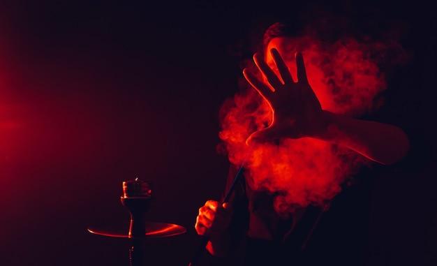L'uomo fuma un narghilè in un bar e soffia una grande nuvola di fumo con luci al neon rosse