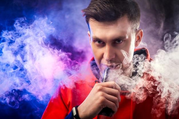 Un uomo fuma uno svapo, fa vapore, studio, fumo colorato.