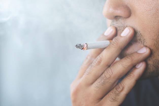 Uomo che fuma una sigaretta. diffusione di fumo di sigaretta.