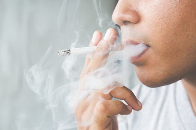 Uomo che fuma una sigaretta. diffusione di fumo di sigaretta