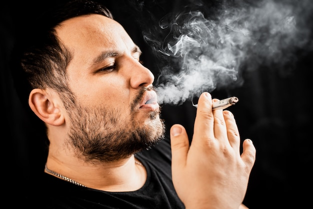 Un uomo che fuma una sigaretta o droga è un dollaro arrotolato, il concetto di dipendenza da dipendenza e spendere soldi orrore