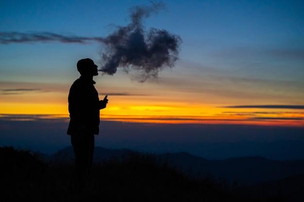 L'uomo che fuma una sigaretta elettronica sullo sfondo del tramonto