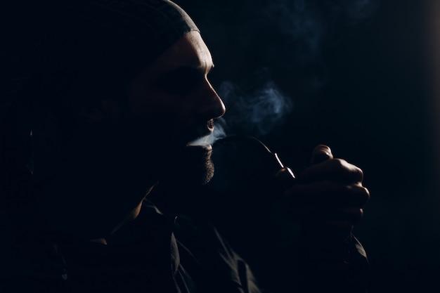 Uomo che fuma la pipa sul buio. ritratto di profilo retroilluminato.