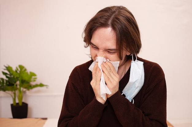 Un uomo starnutisce, una maschera medica. spazio vuoto per il testo su uno sfondo bianco. un uomo malato in quarantena domestica. coronavirus, covid.
