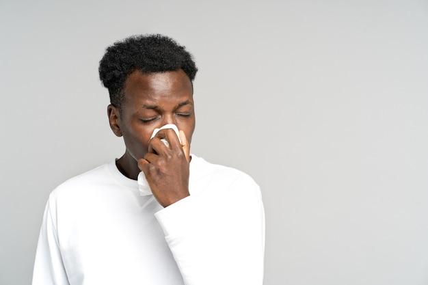 Uomo che starnutisce nel tovagliolo che soffre di allergia stagionale
