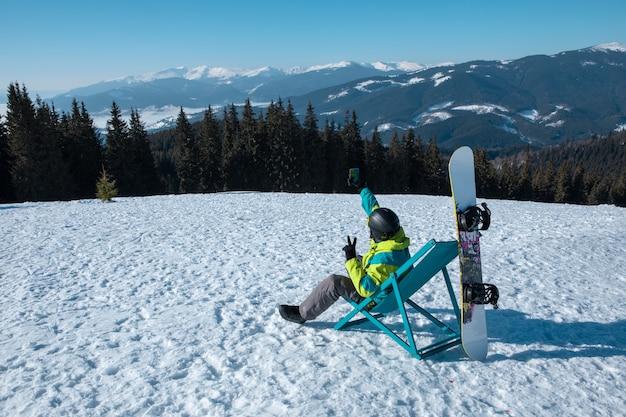 Snowboarder uomo seduto su una sedia che si gode lo spazio della copia con vista sulle montagne