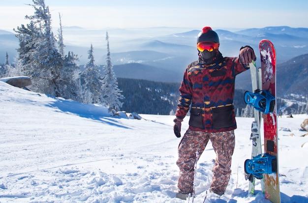 Un uomo in attrezzatura da snowboard sulla cima di una montagna