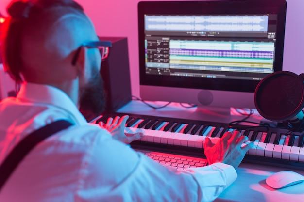 Produttore di suoni uomo che lavora in studio di registrazione.