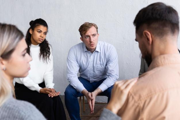 Uomo che parla dei suoi problemi in una sessione di terapia di gruppo