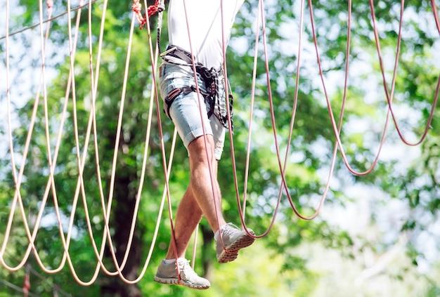 L'uomo trascorre il tempo libero in un corso di corde. uomo impegnato nel parco della corda.