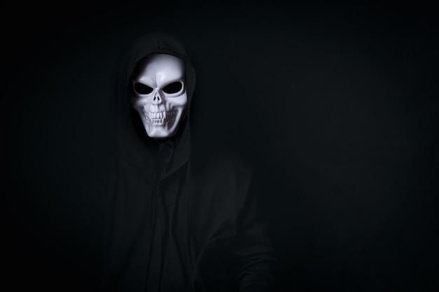 Uomo in cosplay spettrale teschio morto in nero vestito per il festival di halloween