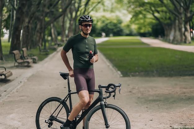 Uomo in abiti sportivi che beve acqua dopo aver pedalato al parco