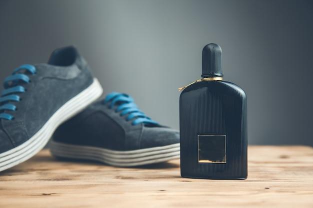 Scarpe sportive uomo e profumo sullo sfondo scuro