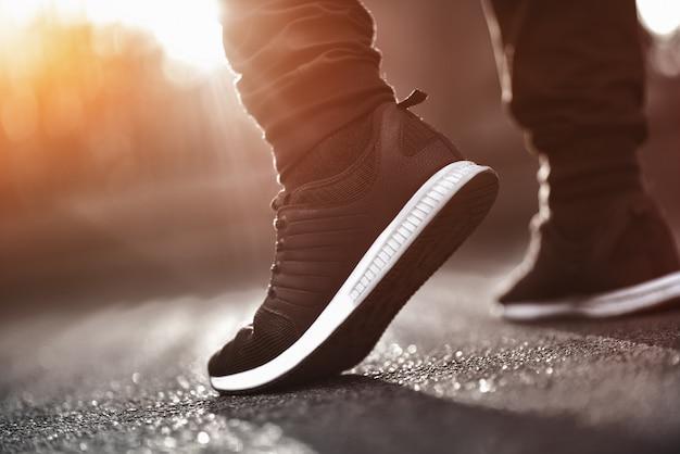 Uomo in scarpe da ginnastica sportive camminando per strada