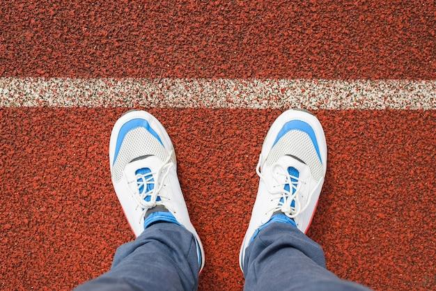 Uomo in scarpe da corsa bianche di sport si leva in piedi sulla pista da jogging rossa nello stadio fuori, primo piano. vista dall'alto, visuale in prima persona