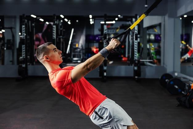Un uomo in abbigliamento sportivo in palestra facendo allenamento con cinghie trx e aggrappandosi alle maniglie. sfida di fitness, vita sportiva