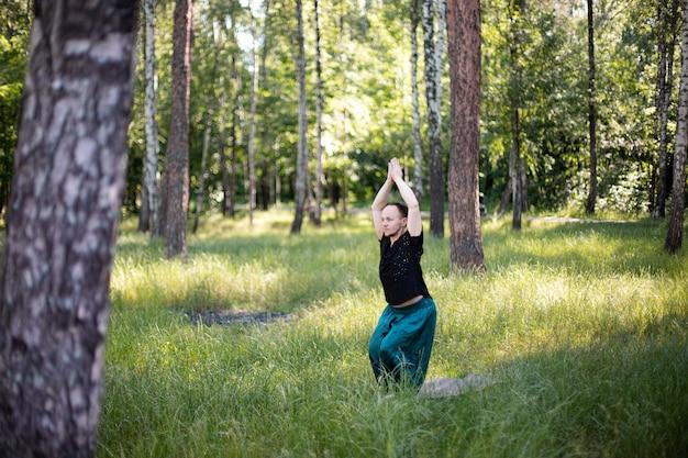 L'uomo in abiti sportivi tiene le mani dall'alto mentre pratica lo yoga nella natura tra gli alberi